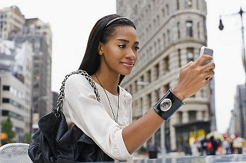 A woman texting on her cell phone while walking down the street