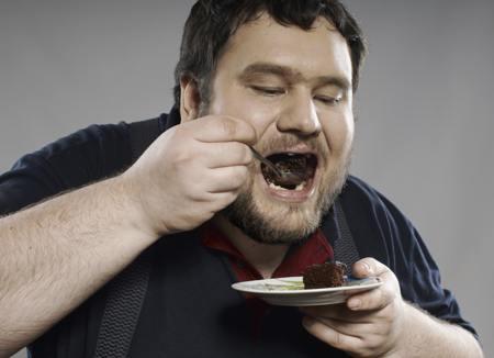 Fat guy eating chocolate cake