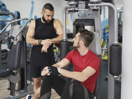 Two men talking in gym