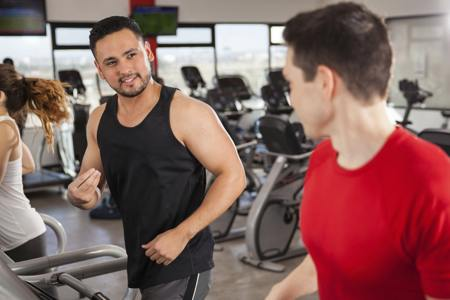 Friends doing cardio and talking at gym